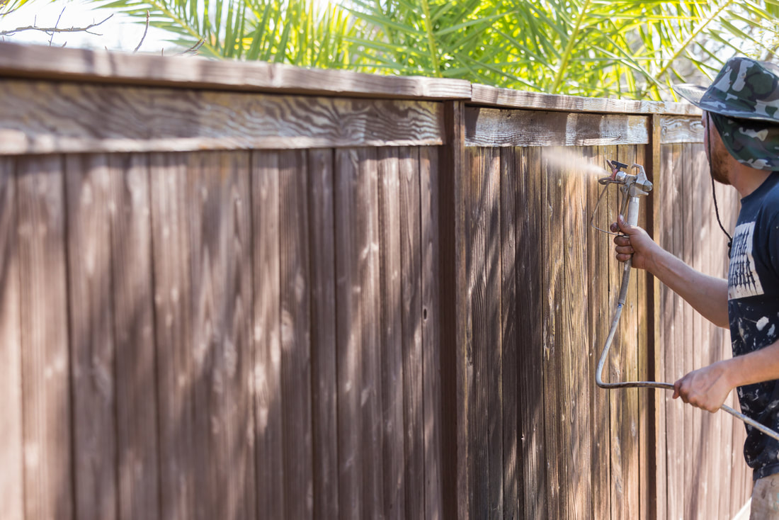 man painting a fence